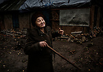 Popasna, eastern Ukraine Nov. 2017.<br /> <br /> Svetlana Nikolaevna Lebed, 62. <br /> <br /> Grad rockets (&lsquo;Grad' is a nickname meaning hail) hit her home 15 minutes after a ceasefire had finished on 14/2/2015, between the Ukrainian army and pro-Russian separatists&rsquo;. <br /> <br /> She was in bed when the rockets struck and is lucky to be alive, but the attack caused extensive damage to her house. With an outside temperature of -8c and no-where else to go, she was forced to stay where she was.<br /> <br /> The walls are cracked and although she has had some minor repairs done to the roof it still leaks severely. The local administration gave her two pieces of tarpaulin for the roof, but despite pleas from a neighbour on her behalf, they wouldn&rsquo;t give her enough to cover the whole roof. <br /> <br /> She bought the property eighteen years ago but doesn&rsquo;t have the official papers for its purchase and so can&rsquo;t qualify for help to rebuild it. <br /> <br /> She cannot afford the electric for heating or fuel for cooking, although sometimes a neighbour from the next village will bring her some hot food. She doesn't receive any support from anyone else.<br /> <br /> Without the necessary repairs to the building, she fears it will fall down and she will be forced to go into an old people&lsquo;s home. &lsquo;I ask God to let me live longer for the sake of my dogs'.