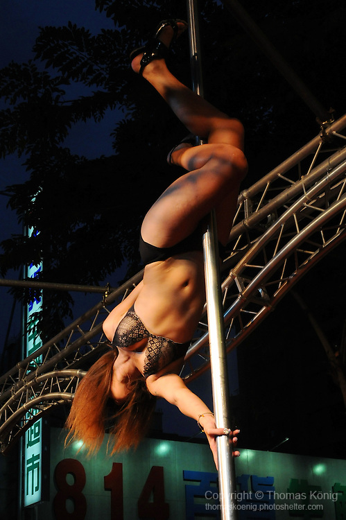 Bao-Jhong Yi-min Temple, Kaohsiung -- Pole dancer showing off her skills at the annual 'Divine Pig' (Shen Zhu) festival during Ghost Month.