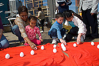Organized by Urban Shaman Donna Henes, participants gather at the South Street Seaport in New York on Saturday, March 20, 2010 to welcome the arrival of spring by standing raw eggs on end.  At the precise moment of the Spring Equinox, this year at 1:32PM, a raw egg can be stood on its end bringing good luck for the rest of the year. Henes has been organizing this event for 35 years.  (© Richard B. Levine)