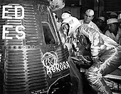 Astronaut Scott Carpenter looks inside the Aurora 7 spacecraft prior to insertion.  McDonnell and NASA capsule technicians along with Astronaut Wally Schirra and John Glenn watch Carpenter prepare for his programmed three-orbit mission at Cape Canaveral, Florida, May 24, 1962. <br /> Credit: NASA via CNP