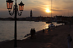 Couple silhouhetted against sun setting in Venice with the background of the Campanille and St Marks square, Venice.