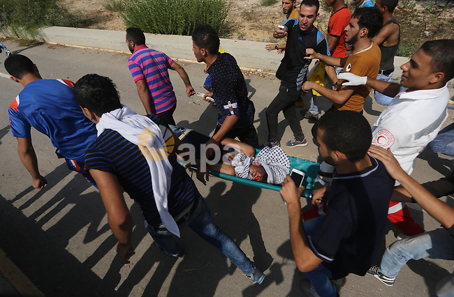 A Palestinian protester is evacuated by comrades after being injured during clashes with Israeli security forces near the Erez border crossing between Israel and northern Gaza Strip on October 13, 2015. A wave of stabbings that hit Israel, Jerusalem and the West Bank this month along with violent protests in annexed east Jerusalem and the occupied West Bank, has led to warnings that a full-scale Palestinian uprising, or third intifada, could erupt. The unrest has also spread to the Gaza Strip, with clashes along the border in recent days leaving nine Palestinians dead from Israeli fire. Photo by Mohammed Asad