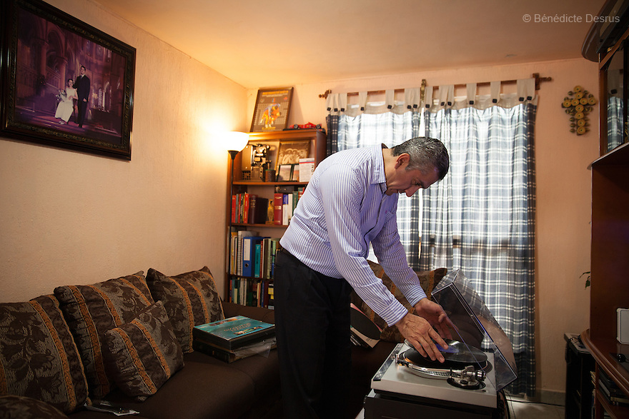 "Donovan listens to classical music on a turntable at his home in Texcoco, Mexico on September 21, 2015. Donovan Tavera, 43, is the director of ""Limpieza Forense México"", the country's first and so far the only government-accredited forensic cleaning company. Since 2000, Tavera, a self-taught forensic technician, and his family have offered services to clean up homicides, unattended death, suicides, the homes of compulsive hoarders and houses destroyed by fire or flooding. Despite rising violence that has left 70,000 people dead and 23,000 disappeared since 2006, Mexico has only one certified forensic cleaner. As a consequence, the biological hazards associated with crime scenes are going unchecked all around the country. Photo by Bénédicte Desrus"