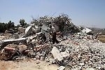 A Palestinian man inspects his house destroyed by the Israeli army bulldozers in Pharaoh village near the West Bank city of Tulkarem, on June 9, 2014. The Israeli army bulldozers demolished the house of a Palestinian family under the pretext of building near the Israeli separation wall. Photo by Nedal Eshtayah