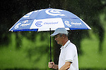 TAIPEI, TAIWAN - NOVEMBER 19:  Jean Pierre Sallat shelters from the rain under an umbrella on the 9th hole during day two of the Fubon Senior Open at Miramar Golf & Country Club on November 19, 2011 in Taipei, Taiwan.  Photo by Victor Fraile / The Power of Sport Images
