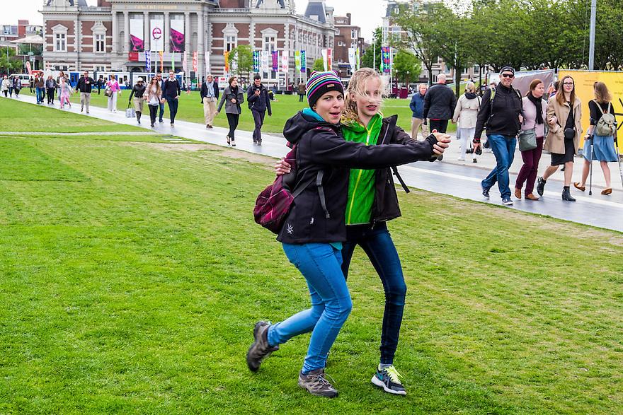 Nederland, Amsterdam, 30 mei 2015<br /> Museumplein. Twee meiden doen een dansje op de muziek van een paar muzikanten op het museumplein.<br /> <br /> Foto: Michiel Wijnbergh