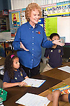 Red headed teacher in blue uniform shirt stands between a mixed black girl and Vietnamese American boy in second grade and explains to child out of picture