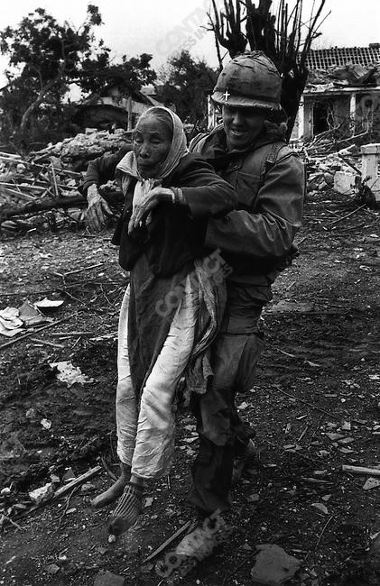 U.S. Army chaplain evacuates a Vietnamese woman, Têt offensive, Battle of Hué, Vietnam, February 1968