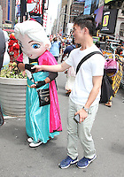 NEW YORK, NY - JUNE 21: Costumed character soliciting a reluctant passerby and attempting to drag him along outside of green zone on the first day of NYPD (New York Police Department) enforcement of the new pedestrian zones in Times Square where costumed characters and those selling bus or show tickets are required to solicit only in the designated green zone in New York, New York on June 21, 2016.  Photo Credit: Rainmaker Photo/MediaPunch