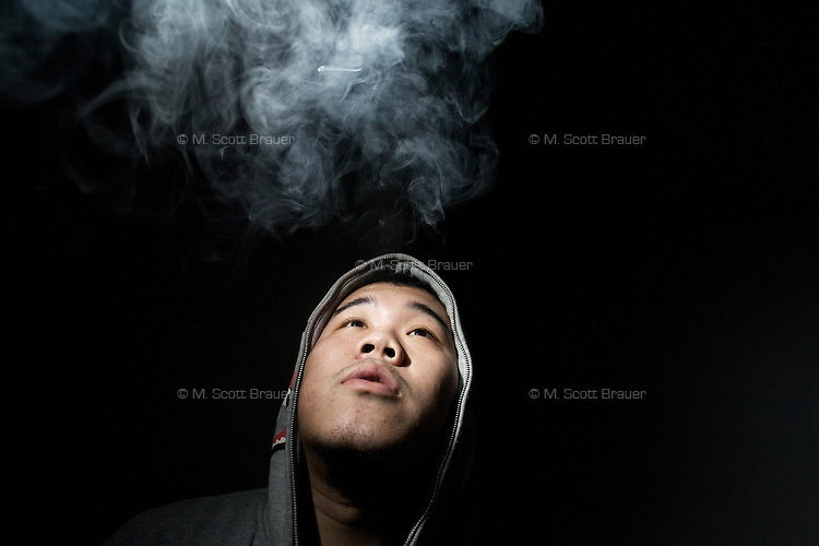 Jobby, guitarist and drummer in the Chinese punk band Overdose, smokes while posing for a  portrait in an apartment in the northern outskirts of Nanjing, China.