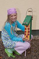 Mädchen, Kind zeigt selbstgebastelten Nistkasten für Wildbienen aus Holz