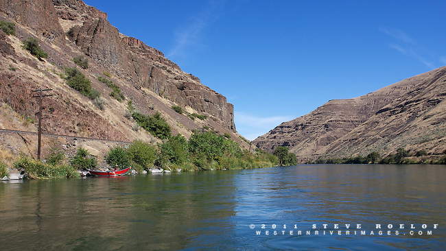 A red drift boat on the Deschutes River.