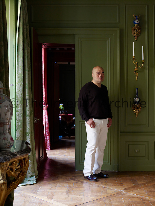 Portrait of designer Andrew Gn in the drawing room of his Paris apartment