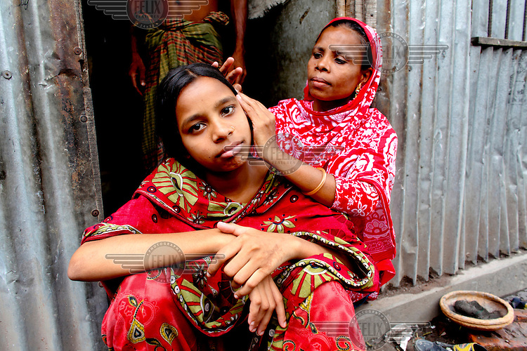 Textile worker Munni spends her Friday off with her mother. Her mother combs her hair in front of their home. <br /> <br /> Textile worker Munni is spending her Friday off with her mother. /Felix Features