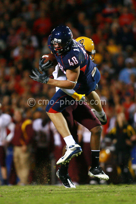 Dec 6, 2008; Tucson, AZ, USA; An Arizona State Sun Devils defender lifts Arizona Wildcats tight end Rob Gronkowski (48) off the ground while making a tackle in the second quarter of a game at Arizona Stadium.  Arizona won the game 31-10.