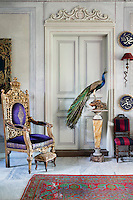 In the entrance of the reception room, a gilded throne-like chair with purple upholstery gives the room a regal touch. Marble flooring is overlaid with an Ushak carpet and Arabic calligraphy ceramic plates hang on the walls.