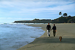 Couple walking dog on Big River beach near Mendocino California
