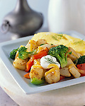 A breakfast plate with omelet, sauteed broccoli and peppers, and potatoes