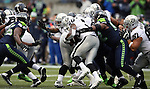 Oakland Raiders running back Darren McFadden (20) is gang tackled by the Seattle Seahawks defensive end Cliff Avril (56) and Brandon Mebane (92)at CenturyLink Field in Seattle, Washington on November 2, 2014. The Seahawks beat the Raiders 30-24 in Seattle. ©2014. Jim Bryant Photo. All rights Reserved.