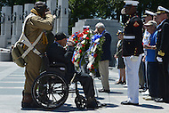 Washington, DC - June 6, 2014: WWII veteran Henry Mendoza (seated) and John McCaskill (left), of the Nation Park Service, salute during a wreath laying ceremony at the National World War II Memorial. The ceremony was part the 70th anniversary of the D-Day invasion honoring WWII veterans. Mendoza was a member of the 9th Air Force in the months leading up to Operation Overlord. (Photo by Don Baxter/Media Images International)