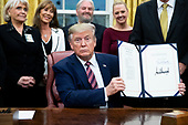 US President Donald J. Trump (C) holds up 'H.R. 724, the Preventing Animal Cruelty and Torture Act', after signing it during a ceremony in the Oval Office of the White House in Washington, DC, USA, 25 November 2019.<br /> Credit: Michael Reynolds / Pool via CNP