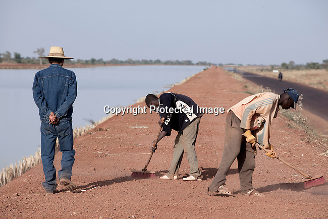 SEGOU, MALI - FEBRUARY 24: Mali workers sweep a road as a Chinese construction manager is nearby at a channel built by Chinese for a Libyan company that leases land from the Mali government on February 24 2011, outside Segou, Mali. The Libyans are planning to do farming in the area. Photo by Per-Anders Pettersson