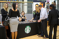 Job seekers at the Starbucks table at a job fair in the East Harlem neighborhood of New York on Wednesday, August 15, 2012.  The job fair is one of the many events occurring during the Harlem Week festivities,  (© Frances M. Roberts)