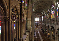 Gothic nave looking towards the chevet, with arcade, clerestory and triforium of stained glass, in the Basilique Saint-Denis, Paris, France. The basilica is a large medieval 12th century Gothic abbey church and burial site of French kings from 10th - 18th centuries. Picture by Manuel Cohen