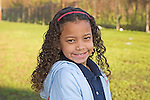 Happy seven year old mixed race of African American descent female child headshot outdoorsin New Orleans, Louisiana