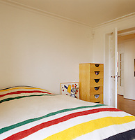 A striped blanket covers the bed in the simply furnished bedroom