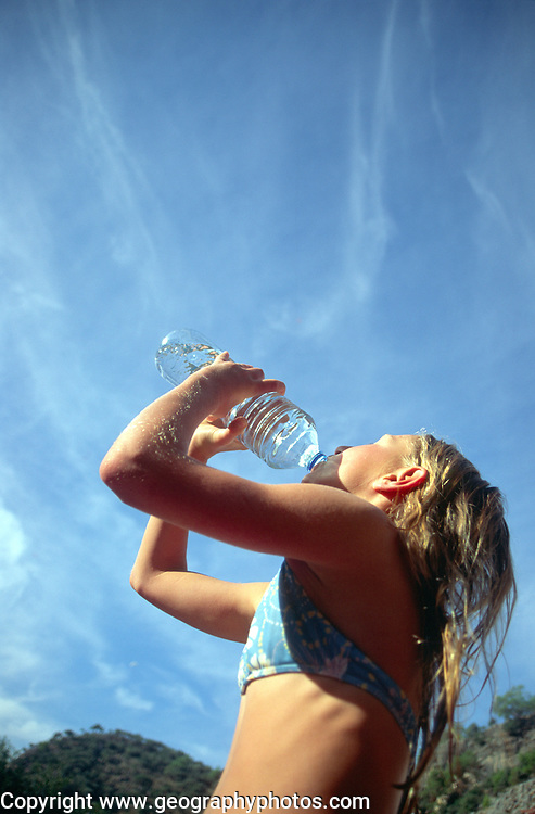 Model released images of girl in swimwear drinking water from bottle