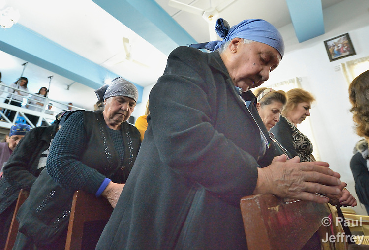 People pray during Mass in Inishke, Iraq, on April 10, 2016. Present was Cardinal Timothy Dolan, the archbishop of New York and chair of the Catholic Near East Welfare Association. He came to Iraqi Kurdistan with other church leaders to visit with Christians and others displaced by ISIS. Along with other church leaders, he celebrated Mass in the Chaldean Catholic church with local residents and displaced Christians living in local villages.<br /> <br /> CNEWA is a papal agency providing humanitarian and pastoral support to the church and people in the region.