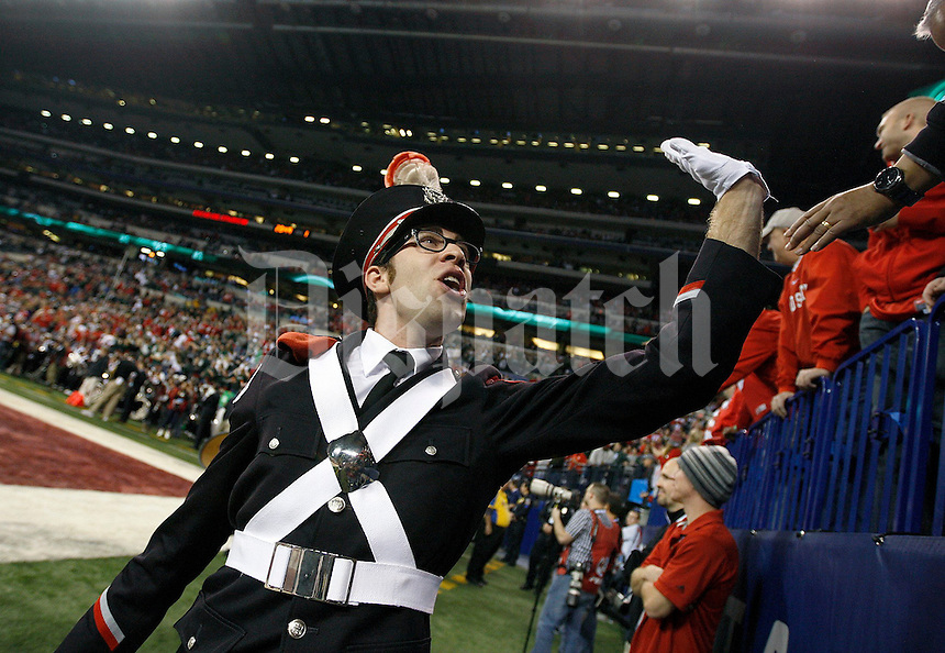 A band member high fives fans prior to the Big Ten Championship football game at Lucas Oil Stadium in Indianapolis on Friday, December 7, 2013. (Columbus Dispatch photo by Jonathan Quilter)
