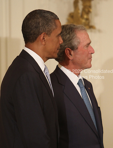 United States President Barack Obama (left) and former U.S. President George W. Bush (right) listen during the unveiling ceremony of the official White House portraits of Bush and former first lady Laura Bush at the White House in Washington, DC, Thursday, May 31, 2012. .Credit: Chris Kleponis / CNP