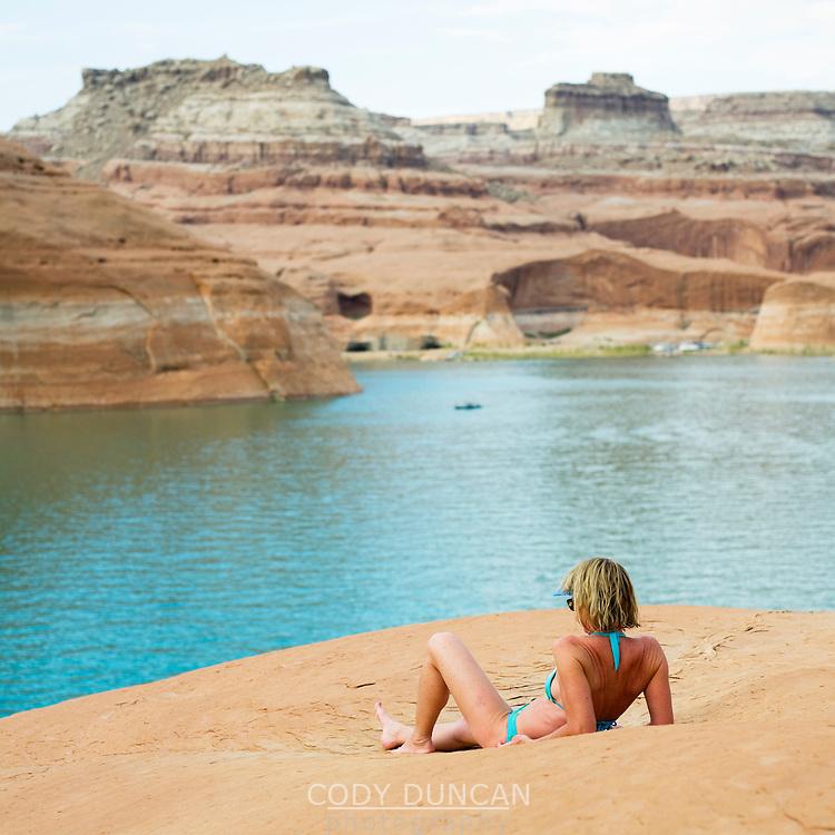 Mature female sunbathing on rocks above lake Powell