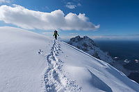 Female hiker ascending winter mountain ridge towareds Mengelsdalstind mountain peak, Moskenesøy, Lofoten Islands, Norway