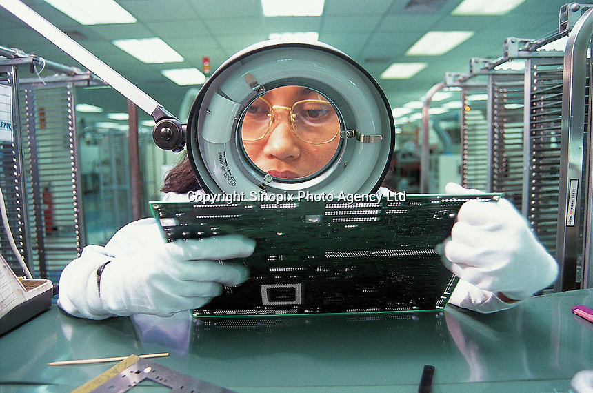 A Filipino labourer checks a circuit board at a computer factory in Taiwan, China.