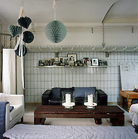 The living room area was converted from a butcher's shop and still has the original wall tiles and barrel ceiling. The use of various shades of blue and grey soften the industrial feel of the room