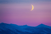 Crescent moon hangs over the Brooks Range mountains, Arctic, Alaska.