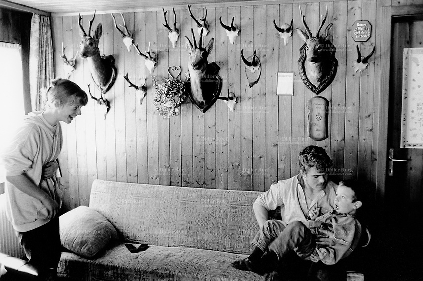 Switzerland. Canton Nidwald. Oberalp. 1500 meters high. Engelberg valley. Brothers and sisters play and laugh together in the living room, where dead does head are fixed on the wood wall. The animals were killed while hunting . Swiss alpine farmers. Alps mountains peasants. © 1997 Didier Ruef