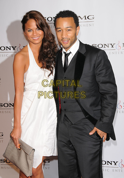 JOHN LEGEND & GUEST.The 2008 Sony BMG Post Grammy Party held at The Beverly Hills Hotel in Beverly Hills, California, USA..February 10,2008              .half length black suit waistcoat white dress clutch bag purse .CAP/DVS.©Debbie VanStory/Capital Pictures