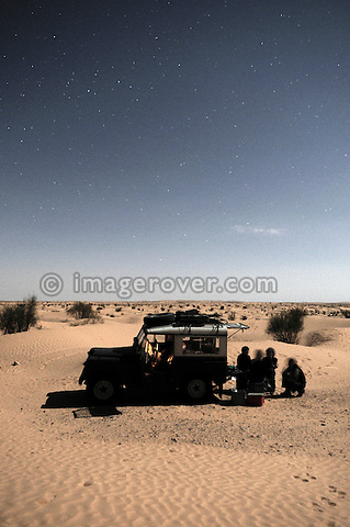 Africa, Tunisia, nr. Ksar Rhilane. Star lit travellers camp at night in the sand dunes on the eastern edge of the Grand Erg Oriental. Some friends planning the next day's drive in their historic 1962 Land Rover Series 2a SWB. --- No releases available, but releases may not be needed for certain uses. Automotive trademarks are the property of the trademark holder, authorization may be needed for some uses.  --- Info: Image belongs to a series of photographs taken on a journey to southern Tunisia in North Africa in October 2010. The trip was undertaken by 10 people driving 5 historic Series Land Rover vehicles from the 1960's and 1970's. Most of the journey's time was spent in the Sahara desert, especially in the area around Douz, Tembaine, Ksar Ghilane on the eastern edge of the Grand Erg Oriental.