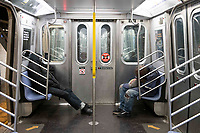 New York, New York City. New Yorkers are told to stay home during the corona virus, (COVID-19) so New York has become eerily empty. The subways are mostly devoid of people, some homeless people take the opportuity to ride the rails and catch a nap.