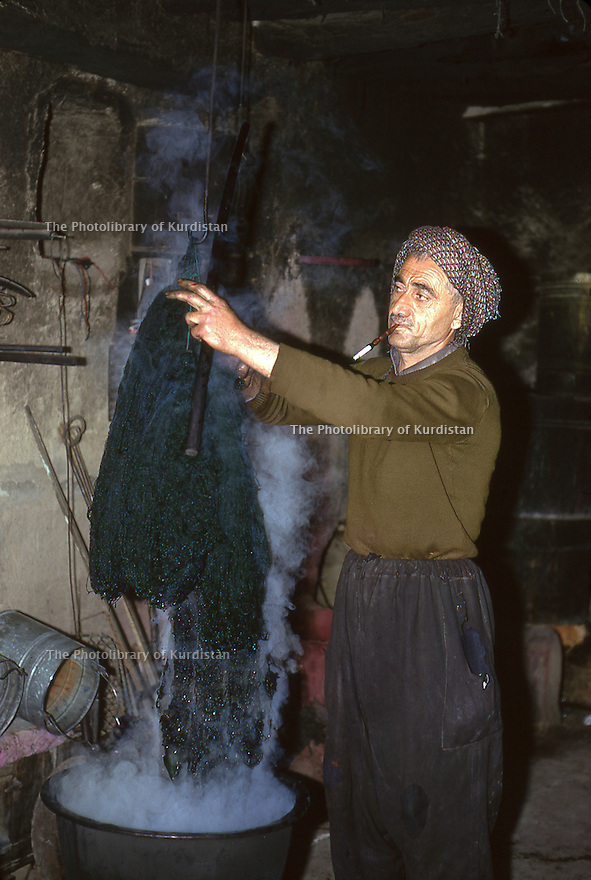 Iran 1975.Mahabad: Man in his shop dyeing wool