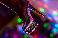 A Salvadoran sex worker's foot in a high heel shoe is seen while waiting for customers in a sex club in San Salvador, El Salvador, 8 April 2018. Sex workers' task in the club is to be an entertaining and seductive companion. Performing erotic dance on the pole they make the customers stay as long as possible and buy relatively expensive alcoholic beverages from which they have a certain share. Sex workers are not obliged to have sexual intercourse with the club customers, they decide themselves, usually according to their current economic situation.