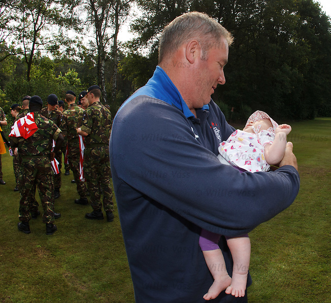 Manager Ally McCoist holds baby Jamie Freya Kate McCoist Lang named after the Rangers legend during a British Army visit to the team hotel in Herzlake Germany