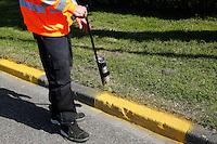 AMSTERDAM- Gemeentewerker spuit een gele markering naast de weg