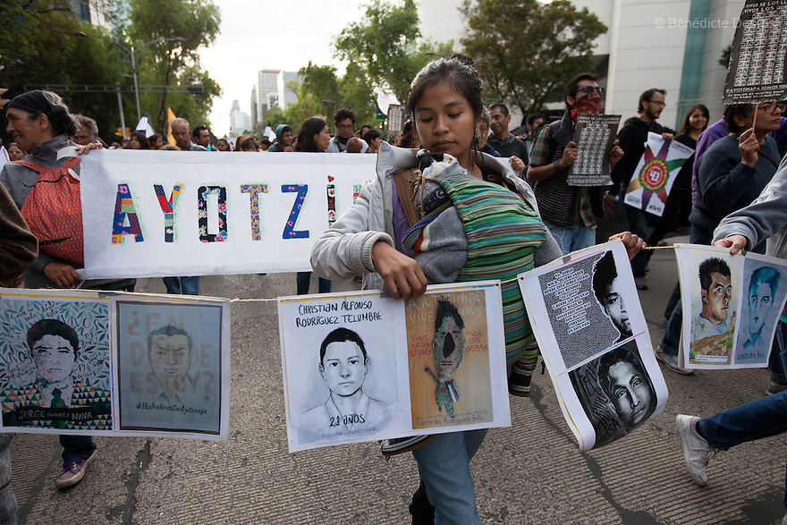 A Mexican woman with her baby holds  illustrations representing the missing students during a march to markthe three monthssince the disappearance of 43 Ayotzinapa's teaching college students in Mexico City on December 26, 2014. The 43students went missingon Sept. 26 after confrontations in which police gunfirekilled six peopleandwoundedat least25inIguala, in Guerrero state. Alexander Mora Venancio, one of the 43 missingstudentsof Ayotzinapa, has been identified and confirmed dead by authorities. Many are demanding justice and that the search for the 42 missing students continue until there is concrete evidence to the contrary. Mexico – officially - lists more than 20 thousand people as having gone missing since the start of the country's drug war in 2006, and the search for the missing students has turned up other, unrelated mass graves.(Photo by BenedicteDesrus)