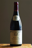 A bottle of Maison Louis Jadot Bourgogne Beaune Boucherottes Premier 1er Cru 2002 red burgundy wine standing on a wooden table top. Backlit backlight back light lit. gray grey background sidelit side light, Maison Louis Jadot, Beaune Côte Cote d Or Bourgogne Burgundy Burgundian France French Europe European