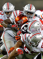 A slew of Ohio State defenders, including linebacker Chris Worley (35), defensive lineman Adolphus Washington (92), linebacker Darron Lee (43) and linebacker Camren Williams (55) stop Virginia Tech Hokies running back Trey Edmunds (14) during the fourth quarter of the NCAA football game at Lane Stadium in Blacksburg, Virginia on Sept. 7, 2015. (Adam Cairns / The Columbus Dispatch)